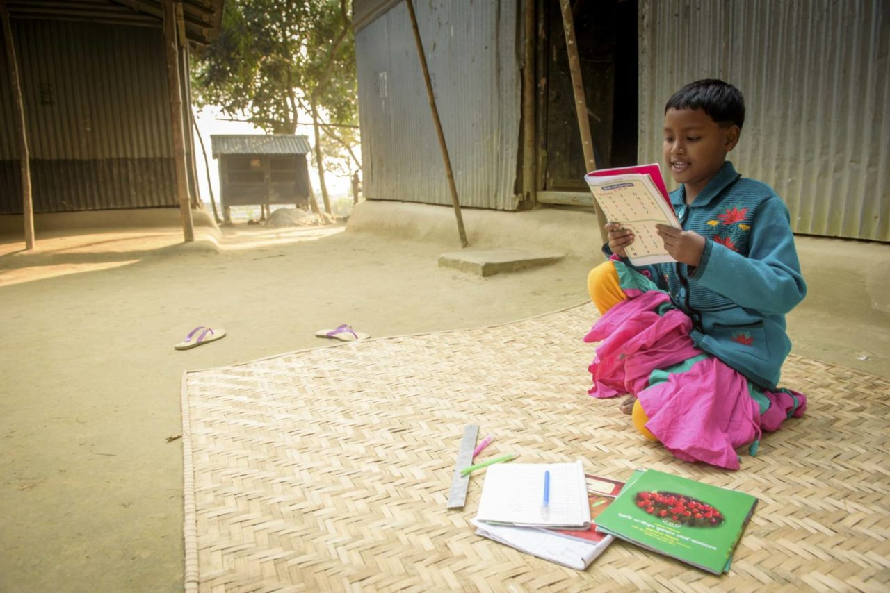 Sonali reads from her school notebook. She dreams of becoming a doctor when she grows up. (©2017 World Vision/photo by Laura Reinhardt)