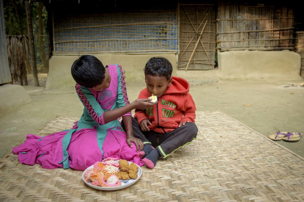 Sonali feeds her brother, Maruf, an egg. Eggs from the chickens they received from World Vision have helped the children move from malnourished to healthy.