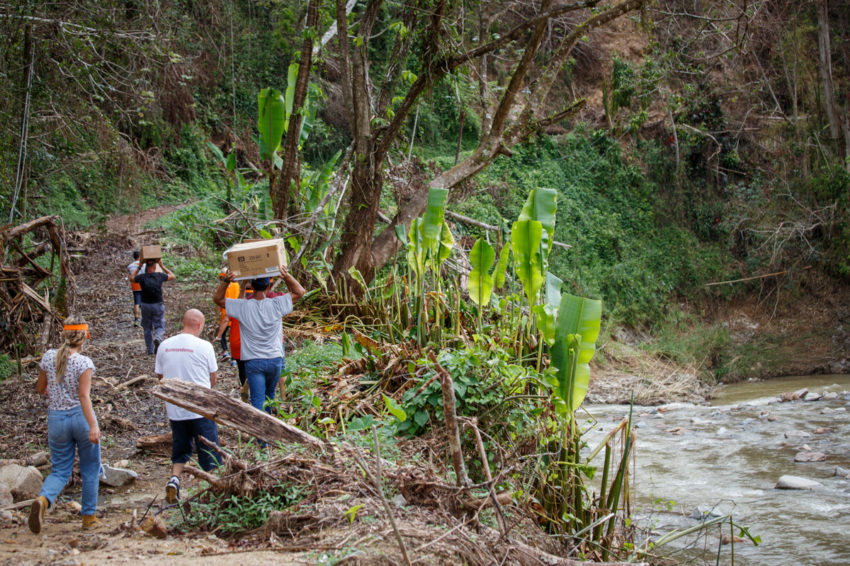 People carrying humanitarian supplies on foot to hard-to-reach homes in Puerto Rico.