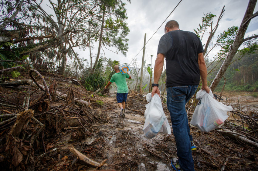 People carrying humanitarian aid on foot to hard-to-reach houses in rural Puerto Rico.