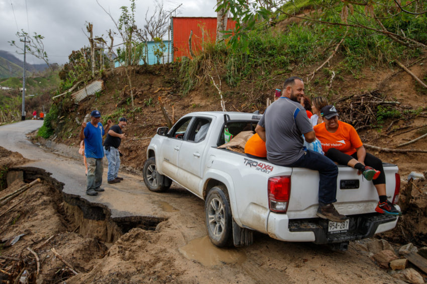 Church members traversing rugged terrain in a truck to deliver humanitarian aid in rural Puerto Rico.