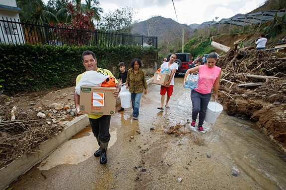 People carry relief supplies from a World Vision distribution following Hurricane Maria in Puerto Rico. (©2017 World Vision/photo by Chris Huber)