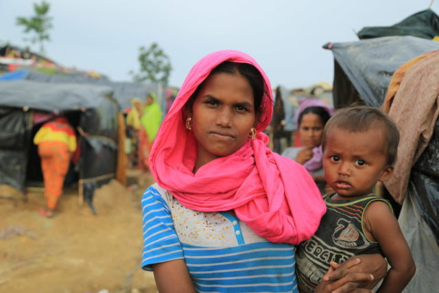 Myanmar refugee in Bangladesh. A woman holds a baby in Jamtoli camp. Impoverished and struggling, refugees are in need of aid.