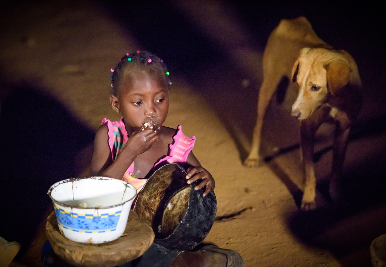 Eunice and Diyo's daughter scrapes the bowl for food. The family doesn't yet have enough to be satisfied, but they're on their way to having more because of a recent gift of goats.