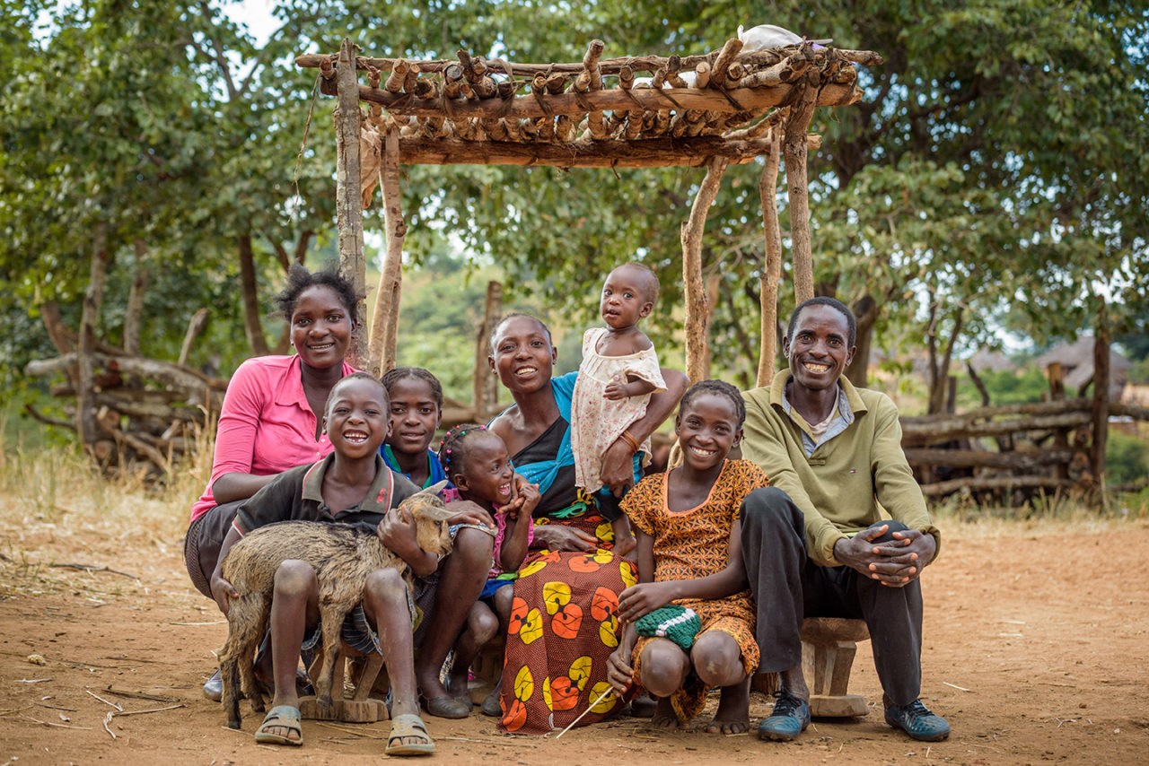 Eunice and Diyo and their family sit with one of the goats they received through the Pass On program.