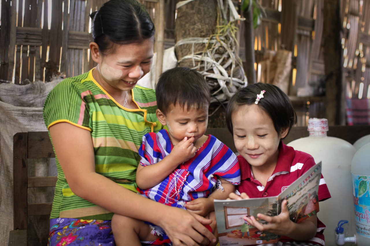 A mother and two children read a Christmas card.