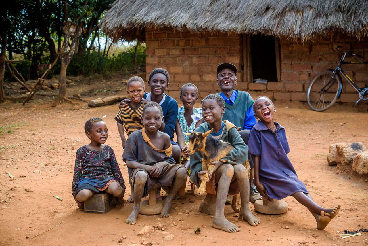 John and Belita sit with their family in front of their home. The goats they received have helped them improve their lives.