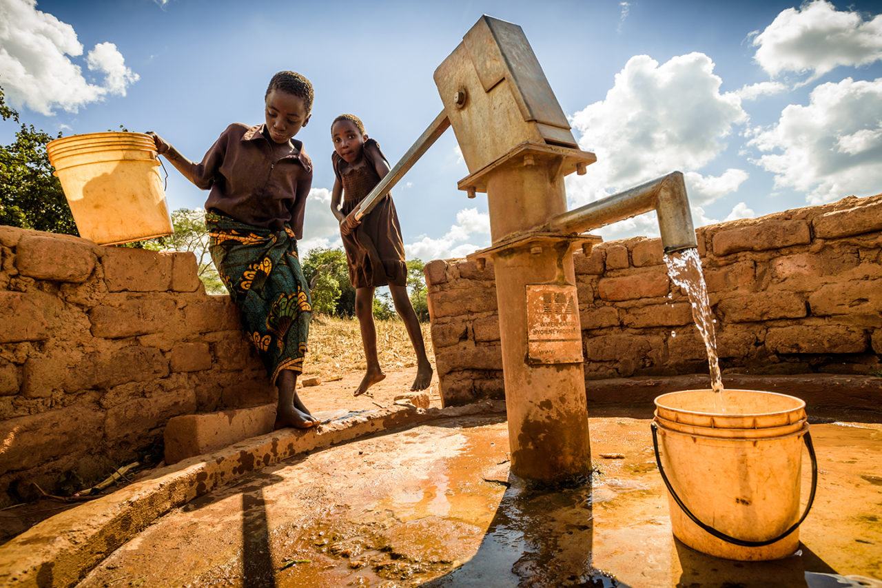 Eight-year-old Miyoba (right) and 10-year-old Matrida help the family by collecting water at a World Vision-built borehole well. Before the well was drilled, the family had to walk 30 to 40 minutes.