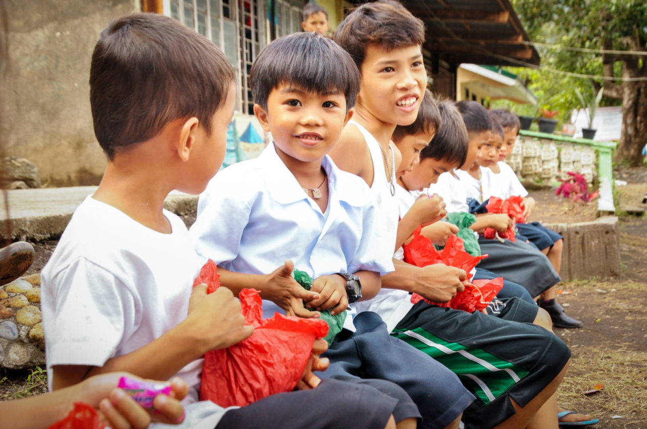 A row of boy students open red and green wrapped presents.