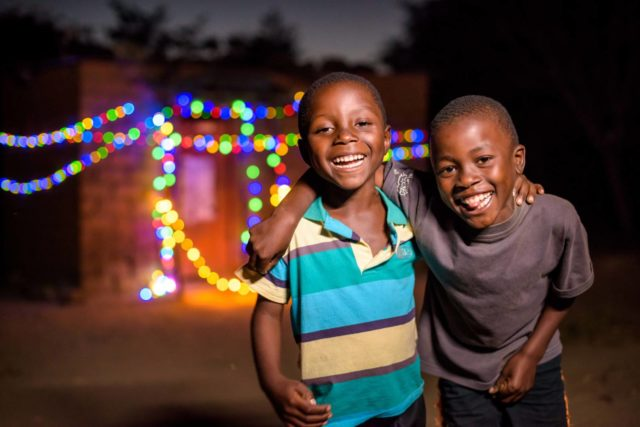 Happy boys smile at night in front of a twinkling house.