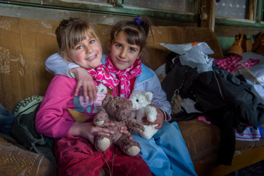 Five-year-old Mariam (left) and her sister, 7-year-old Anahit, are excited about the new stuffed animals and scarves they received that were part of a distribution to help their family. Due to the harsh winter conditions, families in need like the Ghazaryans struggle to find enough money to feed and properly clothe their families. World Vision helps out the families by providing food kits and warm winter clothing and blankets.