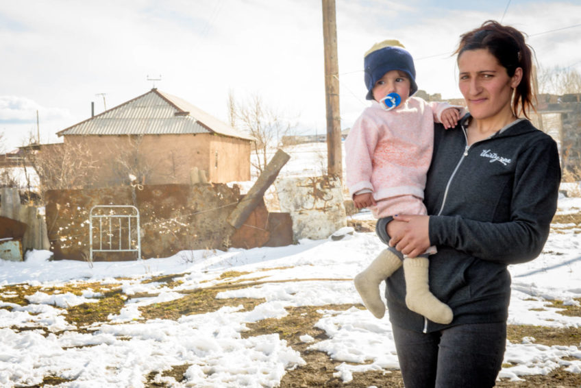 Ani Ghazaryan wears the new hoodie she just received as part of a World Vision warm clothing donation. She's outside her home with her youngest child, 18-month-old Lilit.