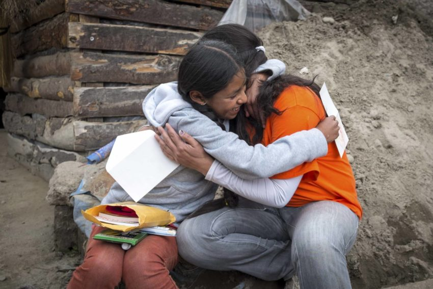A World Vision staff member hugs an 11-year-old girl who received a package from her sponsor. Learn what the Bible says about generosity.