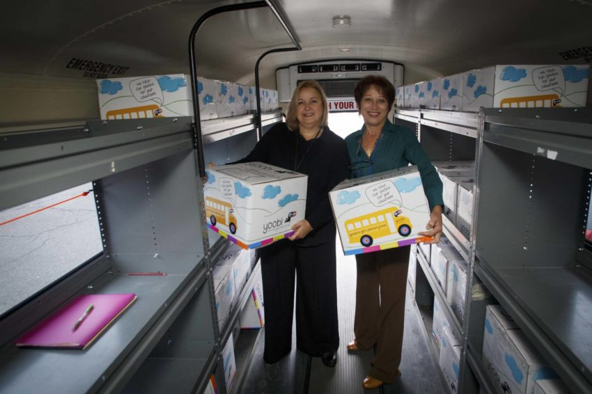 Fifth-grade teacher Susan Depascale, left, and special education para-educator Marianne Papastavaros hold boxes of school supplies in the World Vision Mobile Teacher Resource Center outside their school in Bridgeport, Conn. Women of Vision distributed school supplies to children at various schools in Bridgeport in October 2015. (©2015 World Vision/photo by Chris Huber)