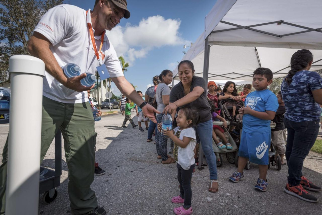 James Orlando, a member of World Vision's Global Rapid Response team, gives water to a little girl during a relief supplies distribution for Hurricane Irma survivors in Florida. (©2017 World Vision/photo by Eugene Lee)