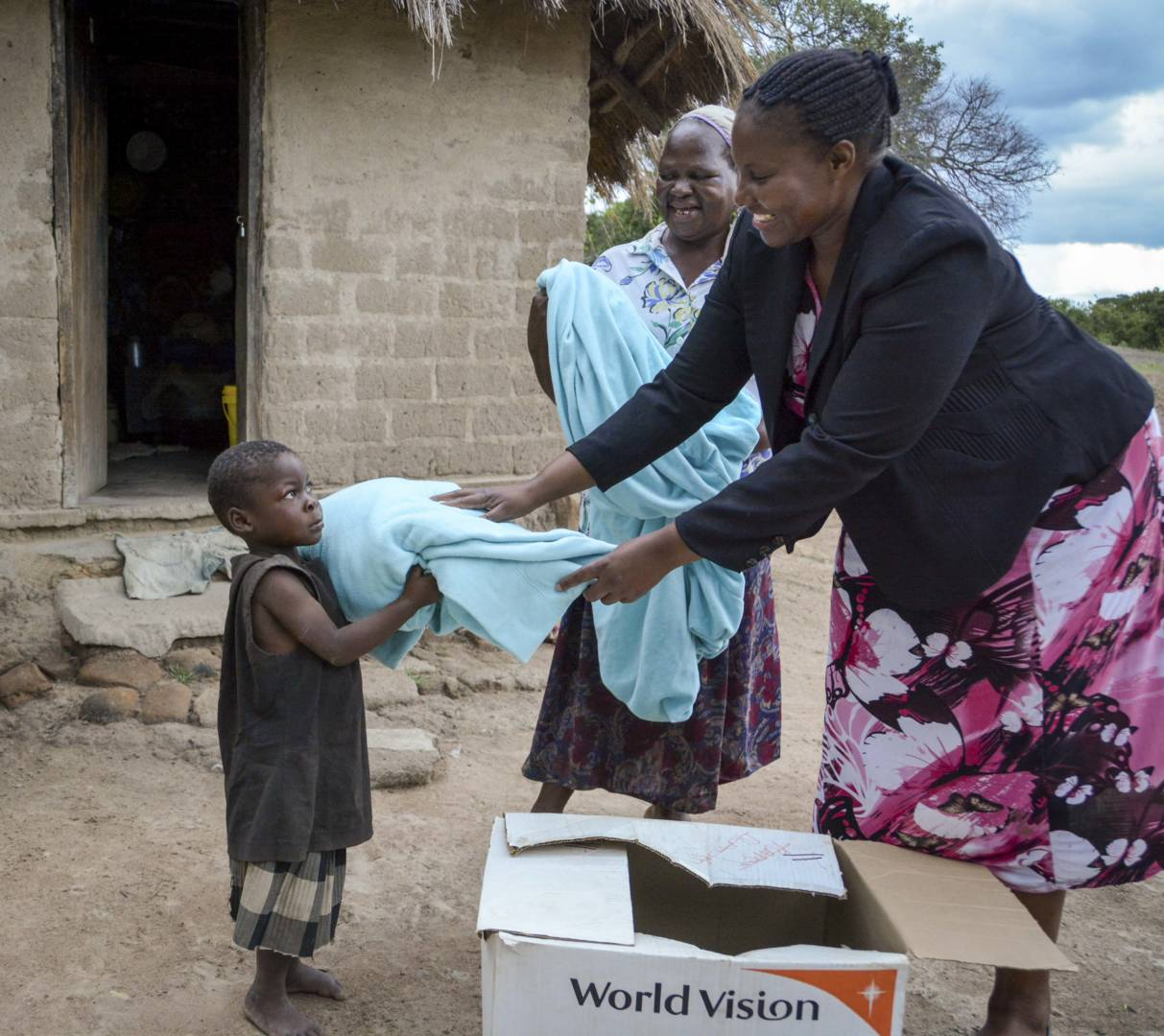 Perpetual Munkpmbwe, a World Vision staff member in Zambia, delivers blankets to Grenda and her grandmother, Rosina. (©2015 World Vision/photo by Collins Kaumba)