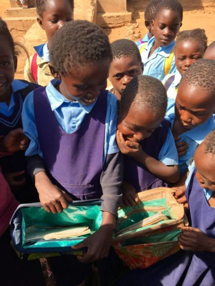 Girls in Zambia examine their new school bags with excitement.