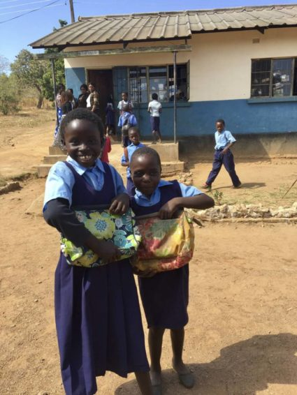 Girls in Zambia show off their new school bags with excitement.