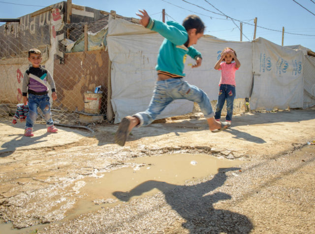 Child leaping in the air with two children looking on in refugee settlement.