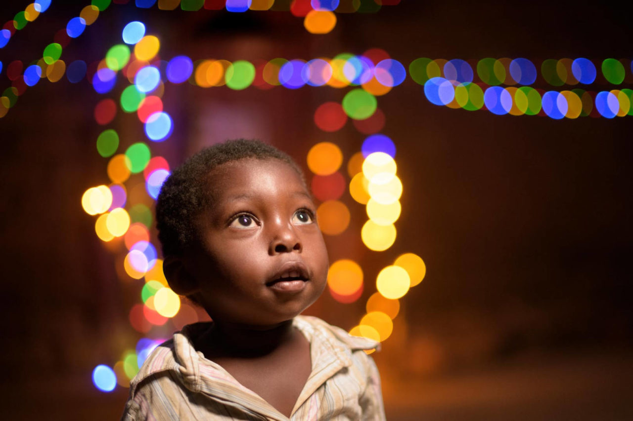 Zambian girl looking up with Christmas lights in background.