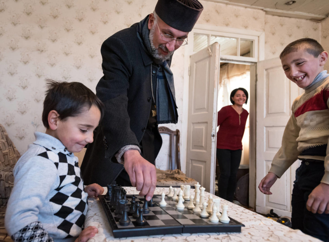 Armenian priest playing chess with a family.