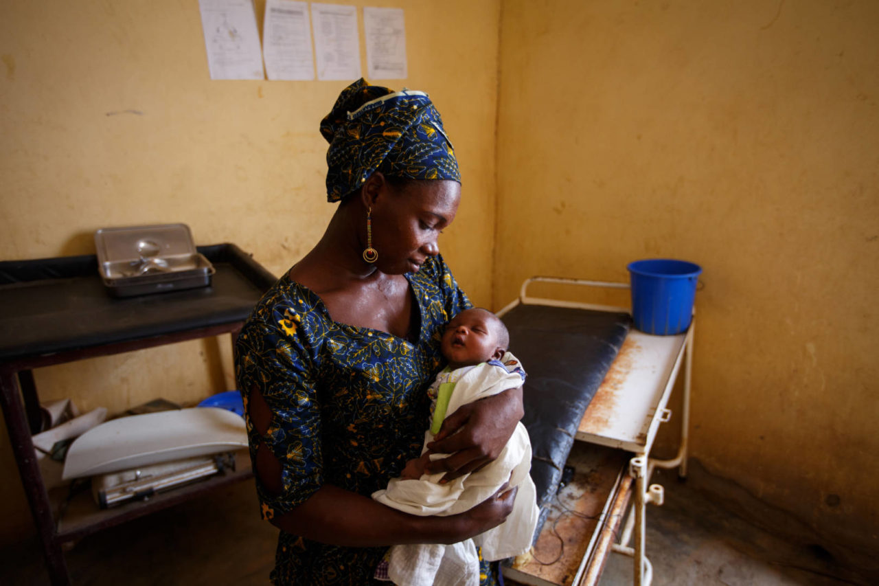 Woman holding and looking at her baby in a health clinic in Mali.
