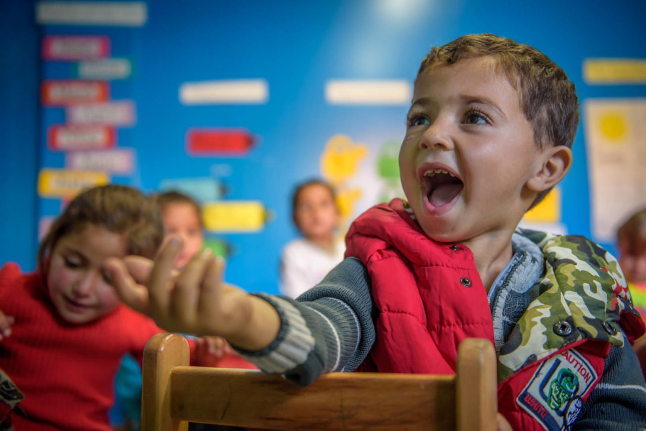 Syrian refugee child smiling in a classroom in Lebanon.