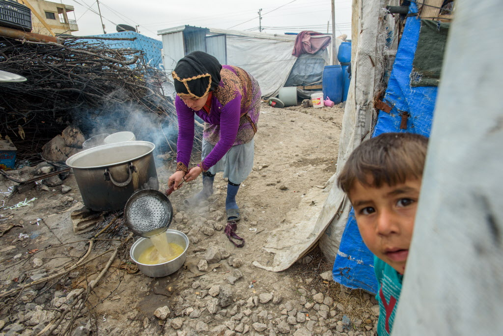Syrian woman cooking food in a pot outside a tent in a refugee settlement in Lebanon.