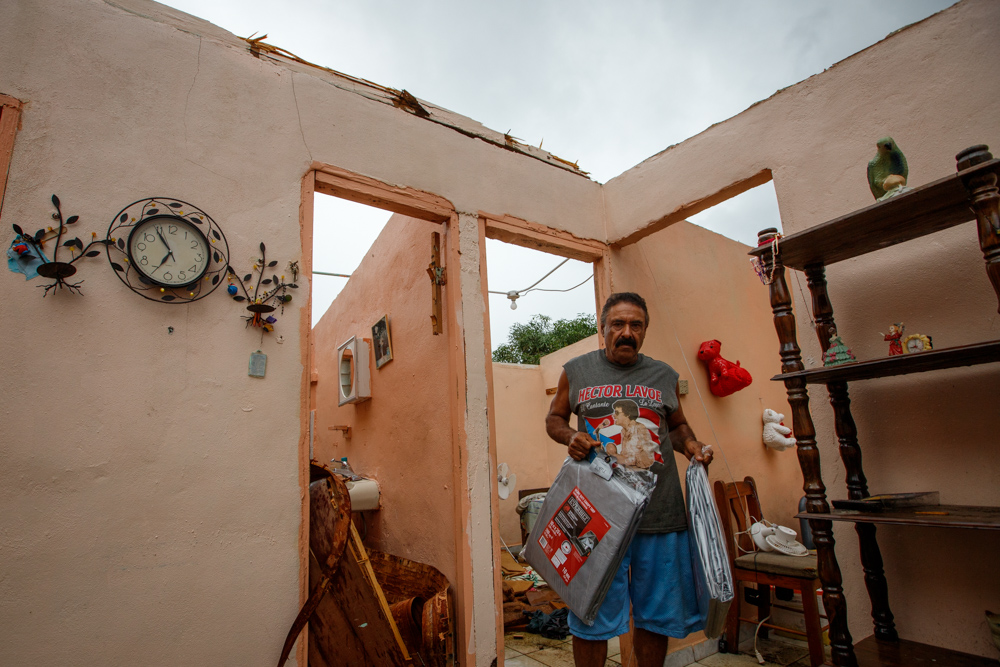 Puerto Rican man holding new tarps while standing in roofless house.
