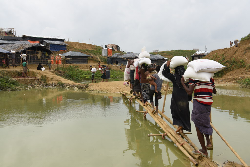 Refugees in Bangladesh walking across a log carrying food supplies.