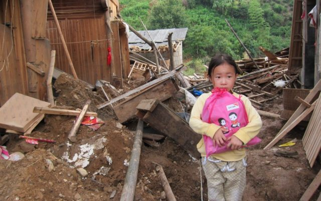 A girl clutches a bag amid destruction. Pray for East Asia.