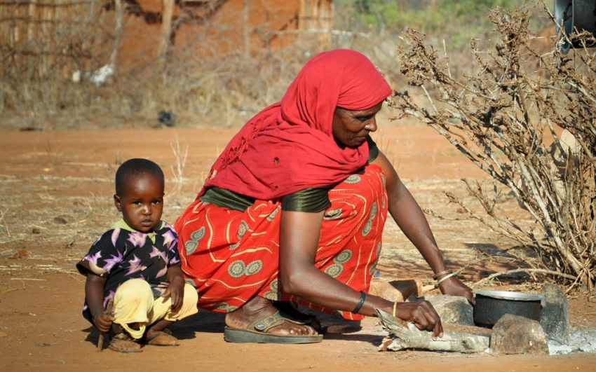 Woman in Kenya cooking outside with her child. Pray for East Africa.