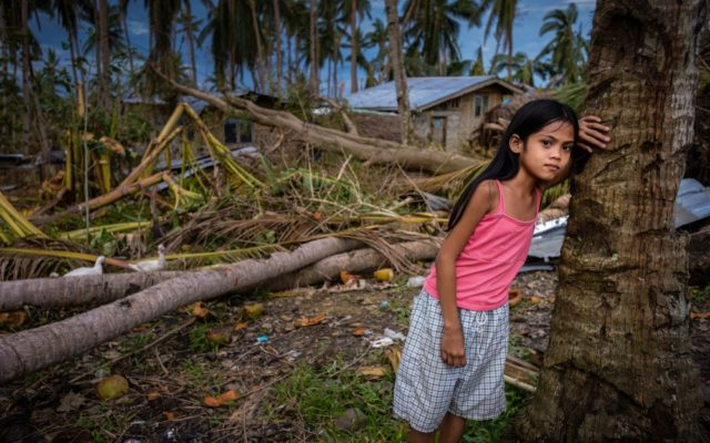 Girl standing against a coconut tree with destroyed house in background in the Philippines. Pray for the Asia-Pacific Islands.