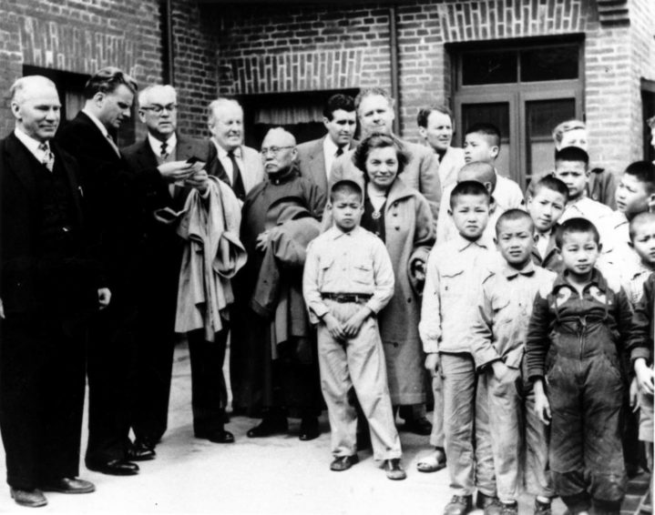 Bob Pierce and Billy Graham with group of children in Asia in the 1950s. (Photo courtesy of World Vision International)
