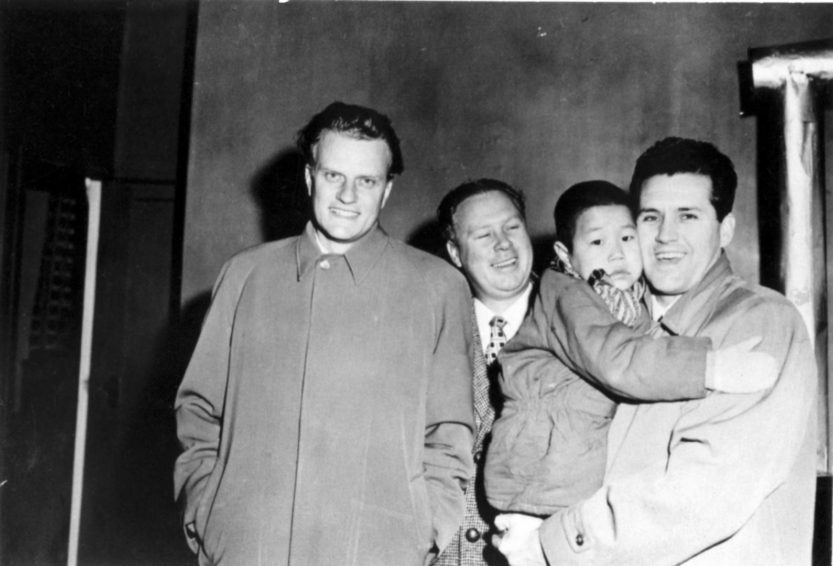 From left to right, Billy Graham, Bob Pierce, and Cliff Barrows, the music director for the Billy Graham Crusades pose with a child. (Photo courtesy of World Vision International)