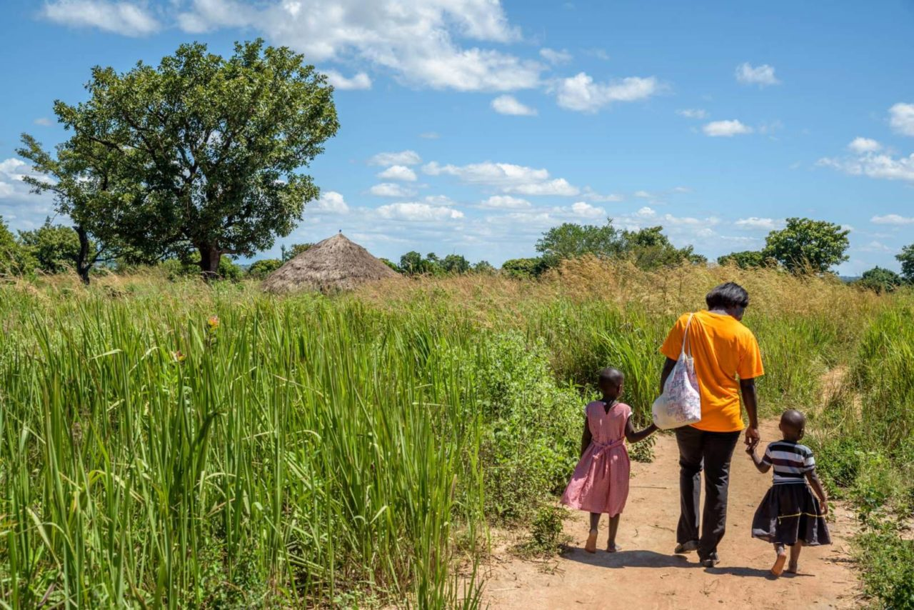 Elizabeth Aluka walks with Grace, left, and Judith, right. In Morungatuny, Uganda, the girls start and end their day with walking to gather water for their family. It's about 6 kilometers of walking every day for them. (©2017 World Vision/photo by Jon Warren)