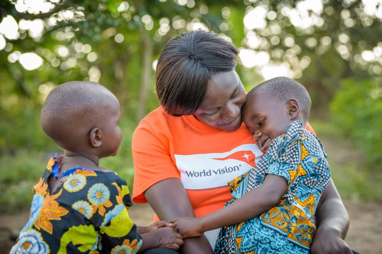 Elizabeth Aluka, a local World Vision manager, talks with Grace, on her lap, while Judith watches. (©2017 World Vision/photo by Jon Warren)