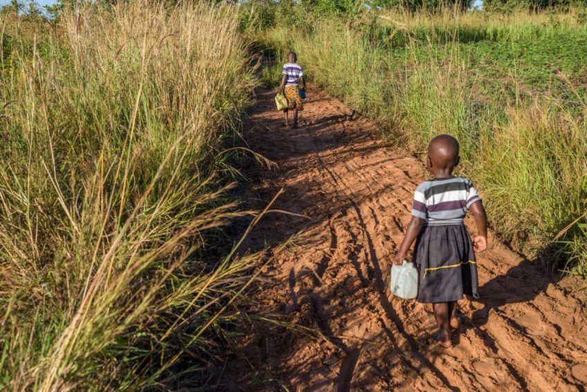 In Morungatuny, Uganda, 5-year-old Grace and 3-year-old Judith start and end their day with walking to gather water for their family. Judith often struggles to keep up with her older sister and has trouble carrying her 1-liter water can. (©2017 World Vision/photo by Jon Warren)