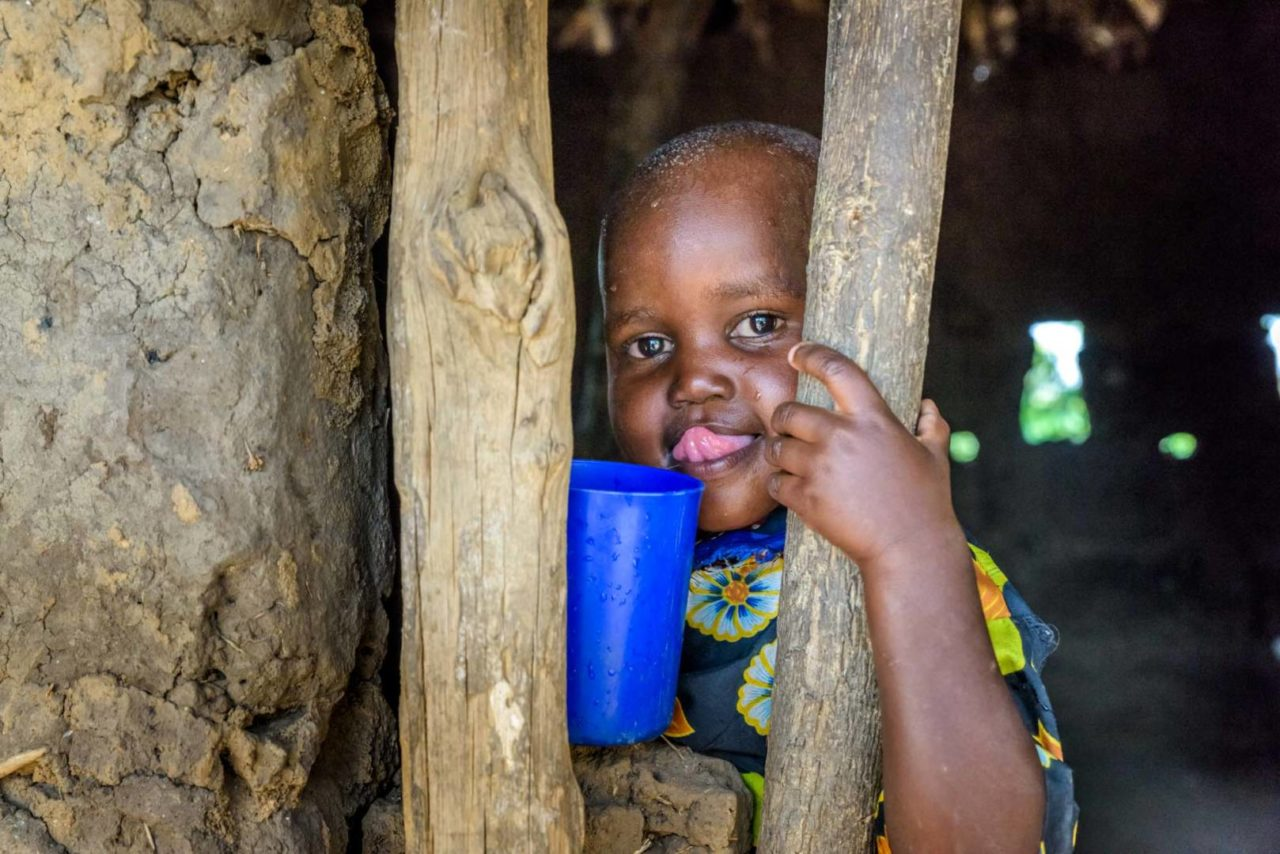 Judith, Grace's little sister, holds a plastic cup of water. The girls drink dirty water every day, and it often makes them sick. (©2017 World Vision/photo by Jon Warren)
