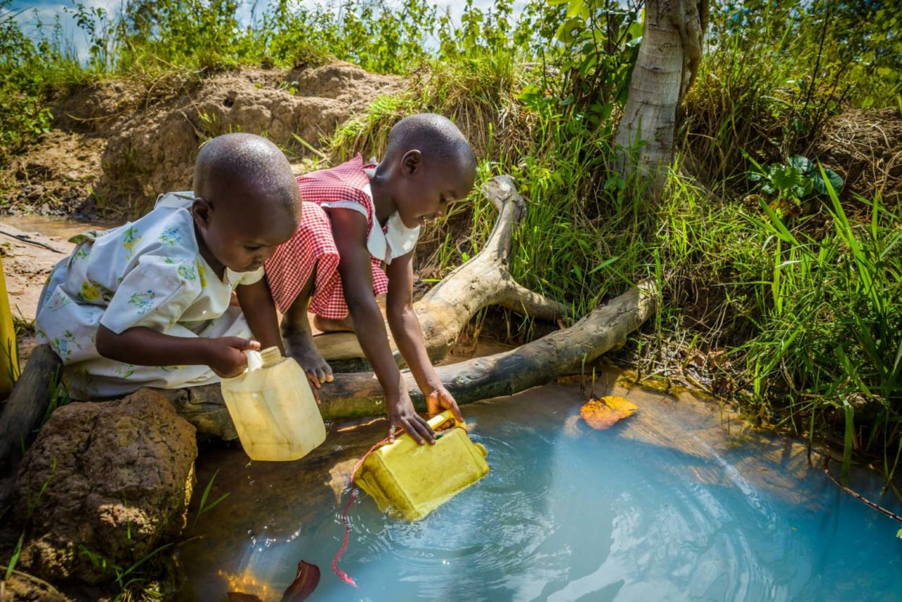 Grace, right, and Judith, left, scoop water from a dirty swamp, which serves as their family's main water source. They make at least two treks a day for water, Grace carrying a 3-liter can, and Judith carrying a 1-liter can. (©2017 World Vision/photo by Jon Warren)
