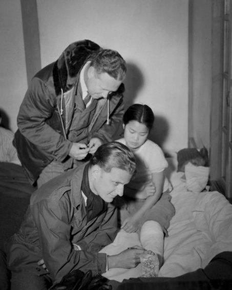 Bob Pierce guides Billy Graham through a hospital during the Korean War. (Photo courtesy of World Vision International)