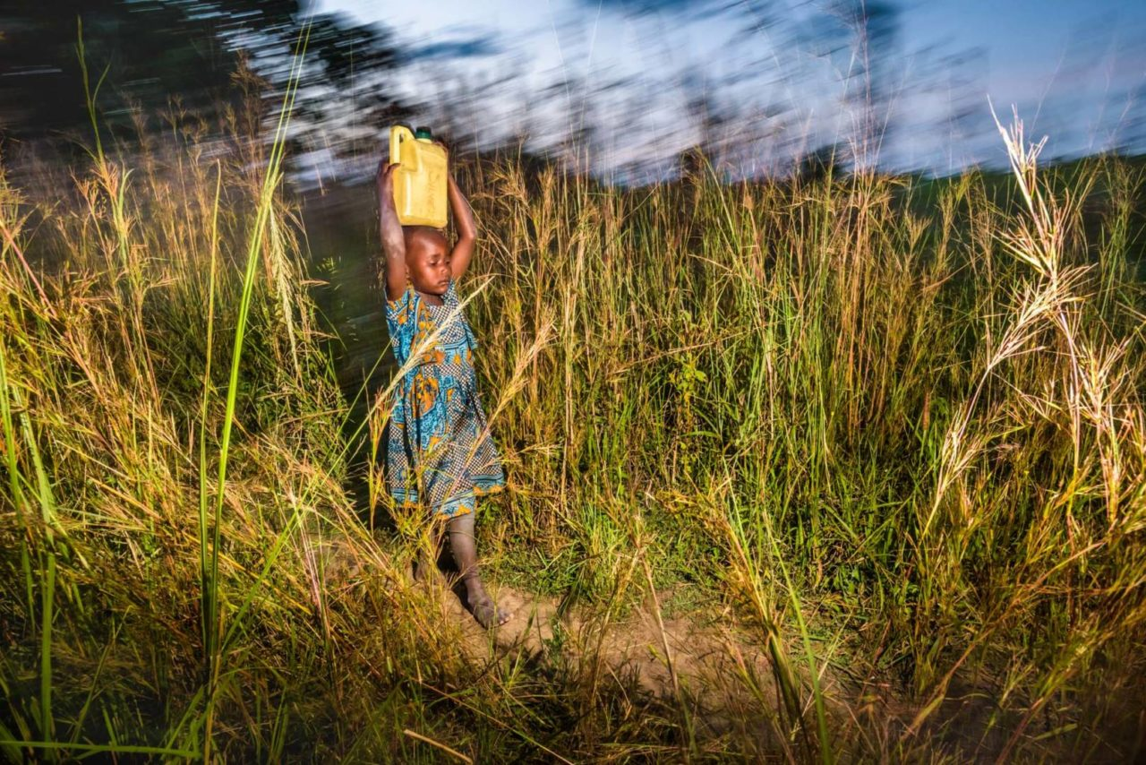 Grace often gets tired and sore from carrying water about 6 kilometers every day. She also suffers from kidney problems because her family can't afford the treatment. (©2017 World Vision/photo by Jon Warren)
