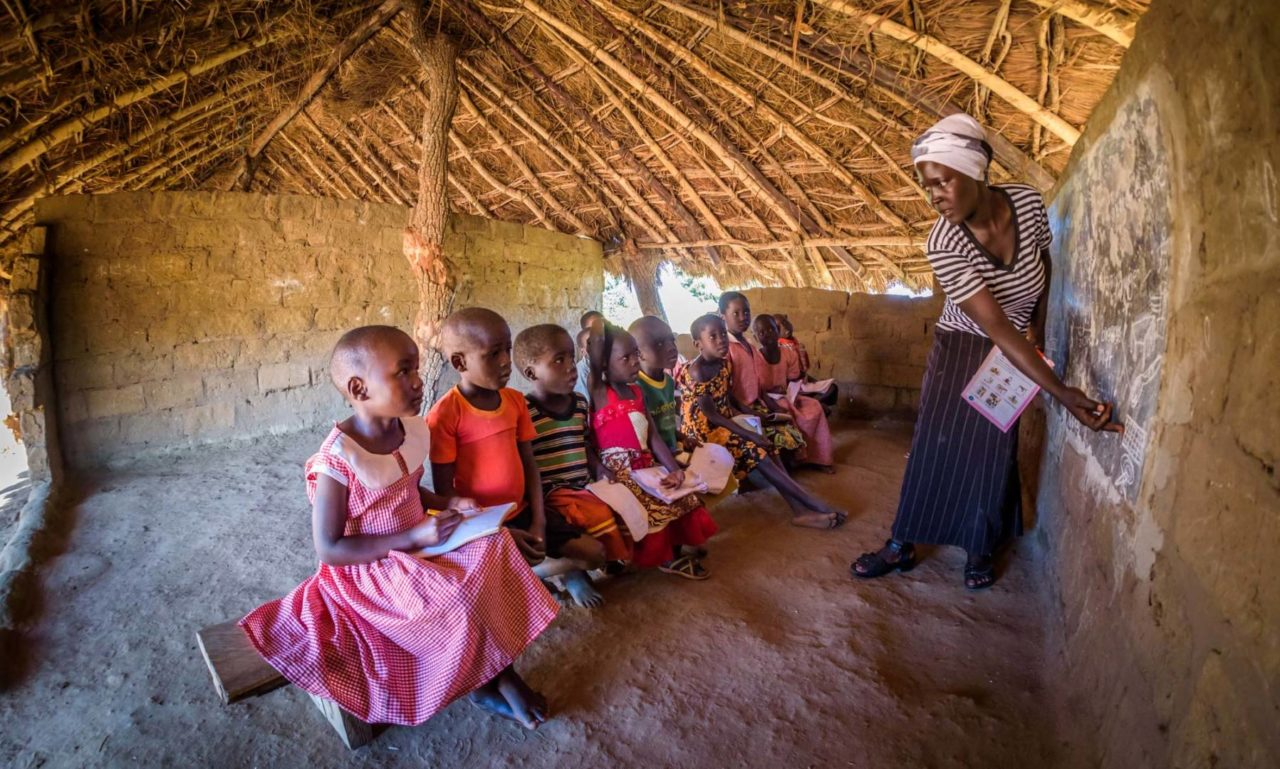 Grace, on the far left in her school uniform, loves to draw and count and dreams of becoming a nurse, but she is about two years behind in her studies because she misses so much school due to how long it takes to get water each day. (©2017 World Vision/photo by Jon Warren)
