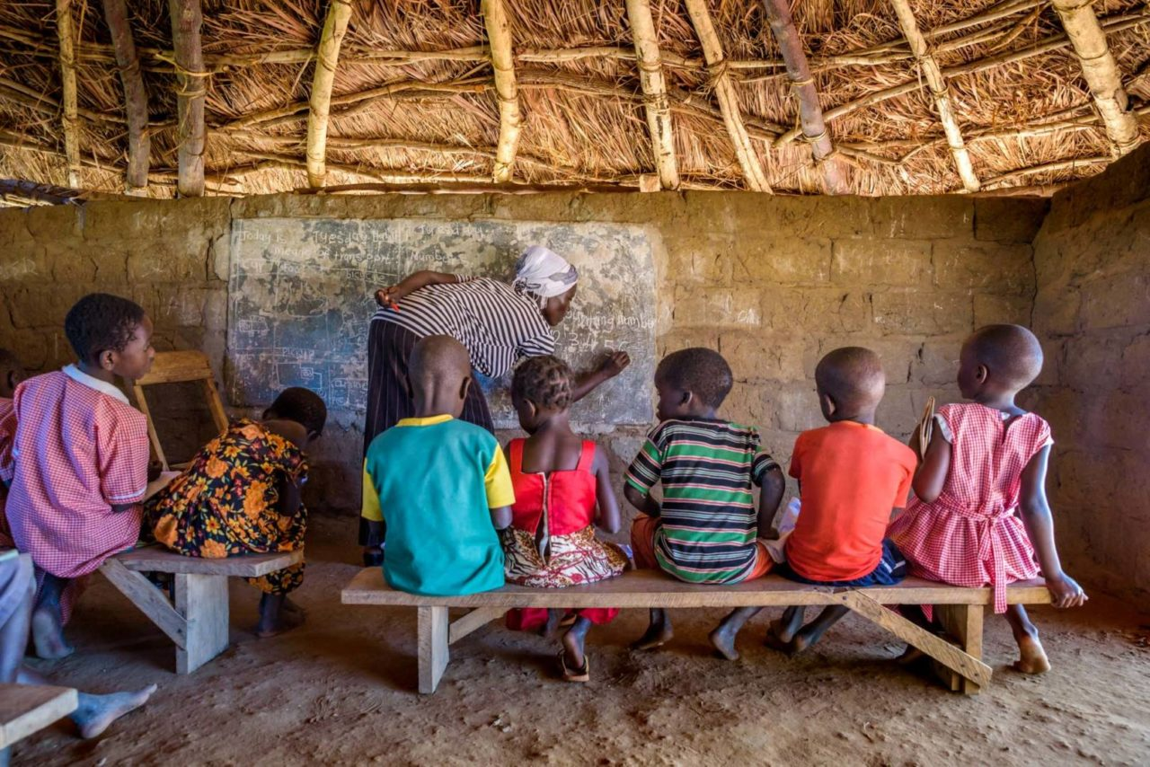 Lucy Acham teaches Grace, far right, and her classmates. There are two levels of preschool and a kindergarten equivalent level all in this class. Grace should be in the kindergarten level, but because she misses so much school, she's at the first preschool level. (©2017 World Vision/photo by Jon Warren)