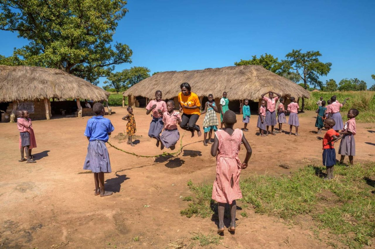 World Vision Area Program Manager Elizabeth Aluka, jumps rope with children at Grace's school in Morungatuny. Elizabeth wove the rope in just a few minutes from nearby grasses, just as she did as a child growing up in a nearby area.(©2017 World Vision/photo by Jon Warren)