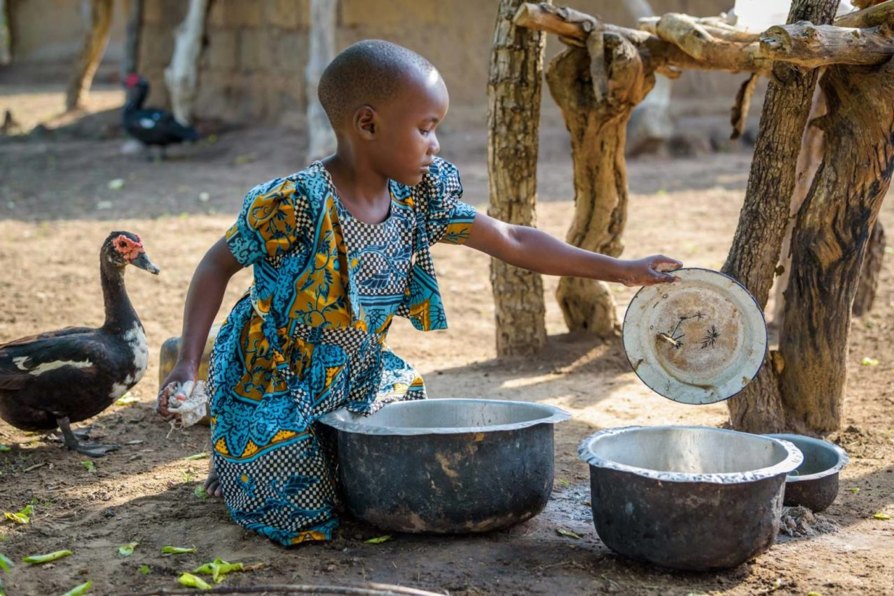 Grace's chores include helping her grandmother, Selina, wash dishes, sweep, and maintain their home. Even though she is only 5, Grace is already aware of all the chores that must be done each day. (©2017 World Vision/photo by Jon Warren)