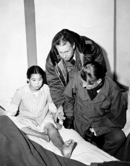 Bob Pierce guides Billy Graham through a hospital during the Korean War. This girl's leg was injured by shrapnel. (Photo courtesy of World Vision International)