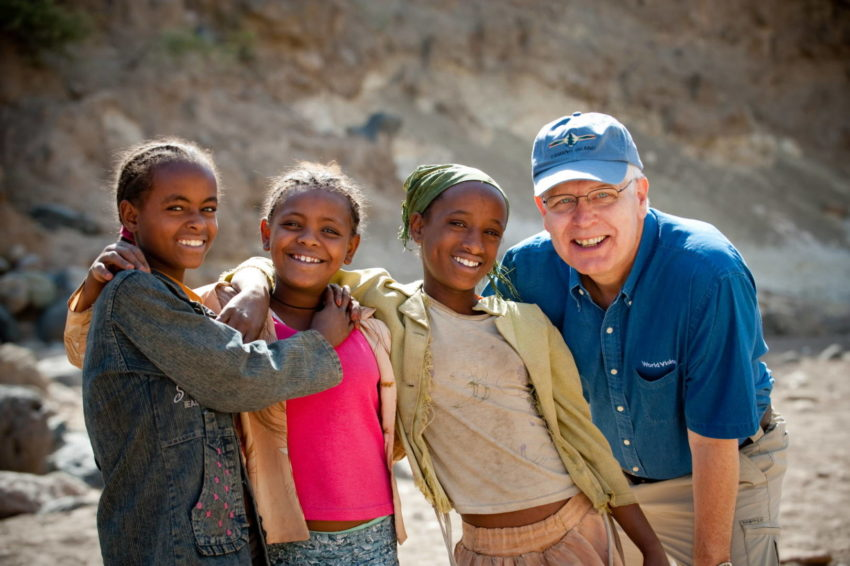 Rich Stearns, World Vision U.S. president, poses for pictures with a group of village girls who have come to collect water in southeastern Ethiopia. (©2009 World Vision/photo by Jon Warren)