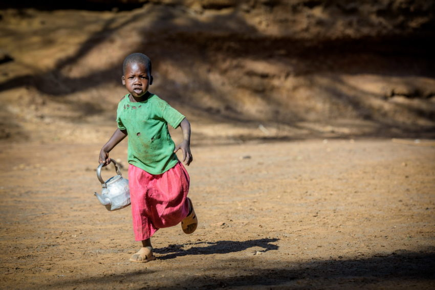 Carrying a tea kettle, Cheru, 5, walks with other children twice a day to dig for water in a dry riverbed in West Pokot, Kenya.