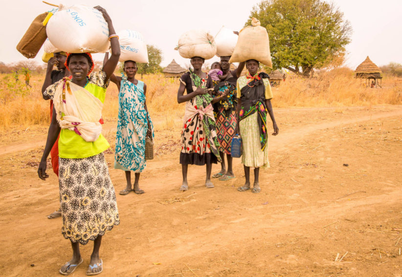 Women carry home food from a monthly distribution from World Vision. Many walked for hours to reach the distribution site in South Sudan. (©2017 World Vision/photo by Stephanie Glinski)